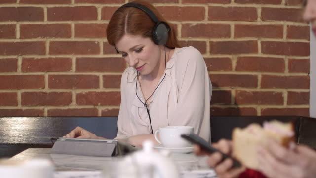vídeos y material grabado en eventos de stock de woman listening music in cafe - auriculares aparato de información