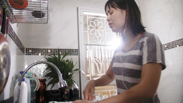 女性は、台所で音楽を聴く - 台所点の映像素材/bロール