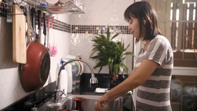 vídeos y material grabado en eventos de stock de escuchar música de mujer en la cocina - frotar