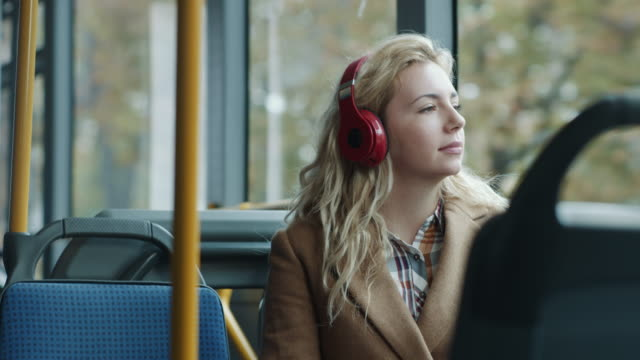 woman listening music on headphones in the bus - tram stock videos & royalty-free footage