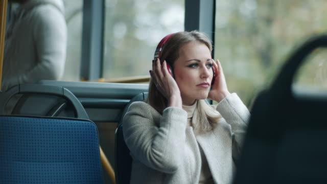 vidéos et rushes de musique d'écoute de femme sur des écouteurs sur le bus - migration quotidienne