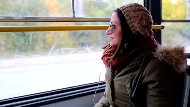 woman listening music on her smart phone in trolley bus - trolley bus stock videos & royalty-free footage