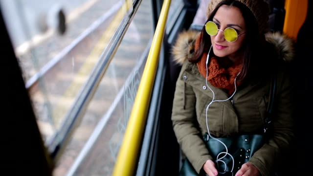 woman listening music on her smart phone in trolley bus - cuffia attrezzatura per l'informazione video stock e b–roll