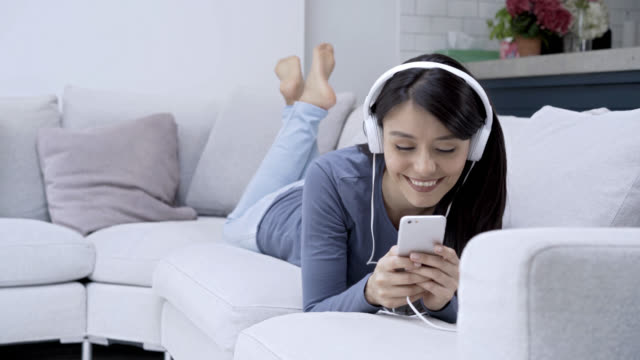 Woman listening music wearing headphones looking at her smartphones