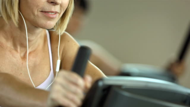 woman listening music while exercising - cross trainer stock videos and b-roll footage