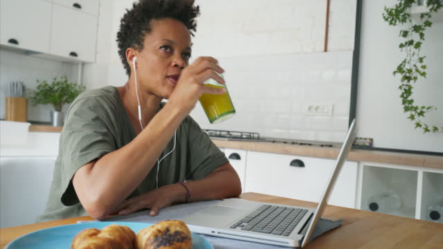 Woman listening podcasts in the kitchen on laptop.