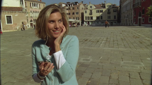 ms pan woman listening to mp3 player and singing in town square / venice, italy - only mid adult women stock videos and b-roll footage