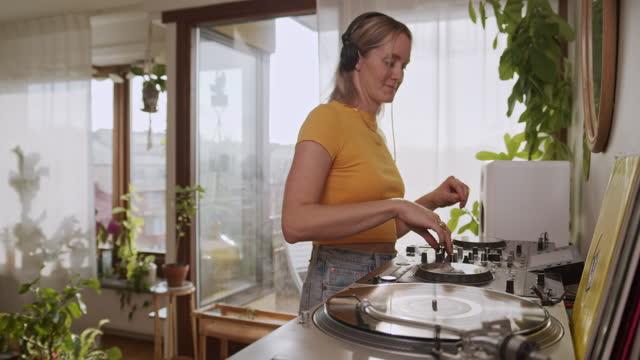 woman listening to music and djing in the livingroom. - hobby bildbanksvideor och videomaterial från bakom kulisserna