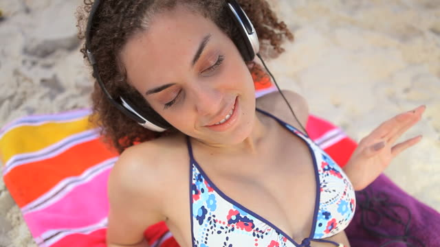 woman listening to music and laughing - bikinioberteil stock-videos und b-roll-filmmaterial