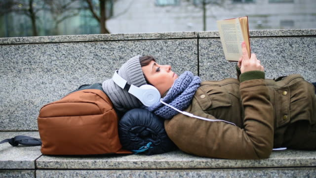 woman listening to music and reading book - lying on back stock videos & royalty-free footage