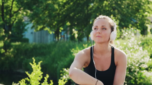 woman listening to music and resting after her exercise in the park - resting stock videos & royalty-free footage