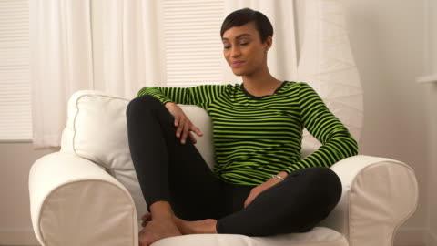 woman listening to music and sitting in sofa chair - endast unga kvinnor bildbanksvideor och videomaterial från bakom kulisserna