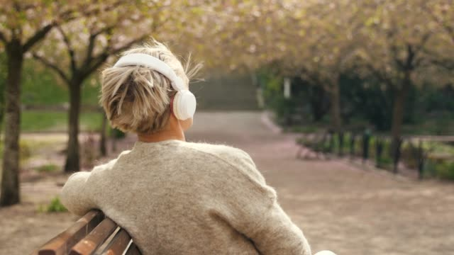 woman listening to music in a park - mature women stock videos & royalty-free footage