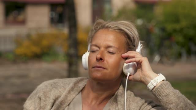vidéos et rushes de femme écoutant la musique dans un parc - 50 54 ans
