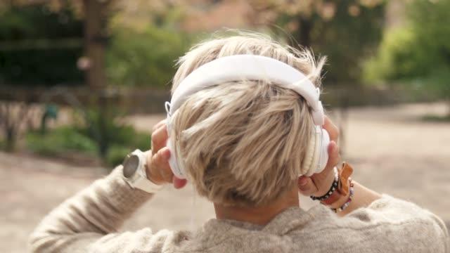 frau hört musik in einem park - rear view stock-videos und b-roll-filmmaterial