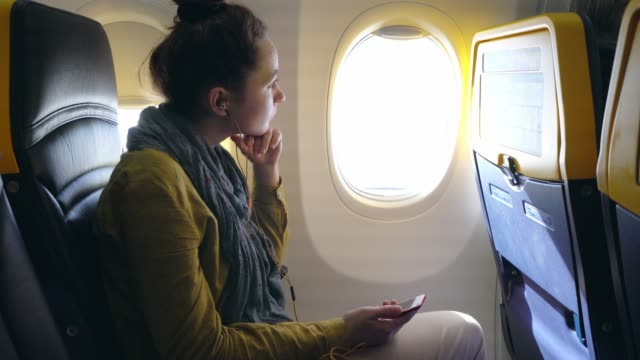 woman listening to music in airplane - looking at view stock videos & royalty-free footage