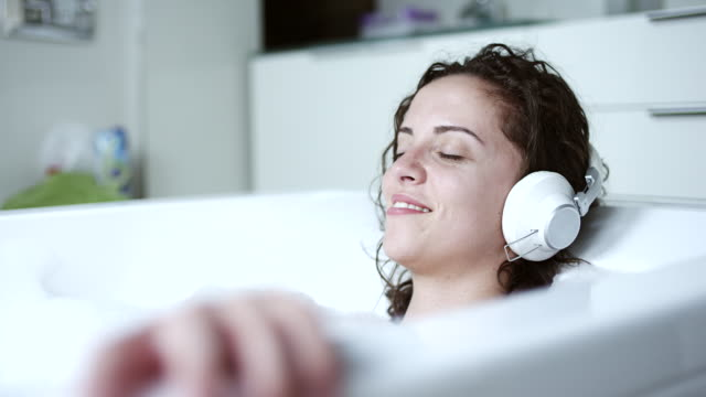 woman listening to music in bathtub - riposarsi video stock e b–roll
