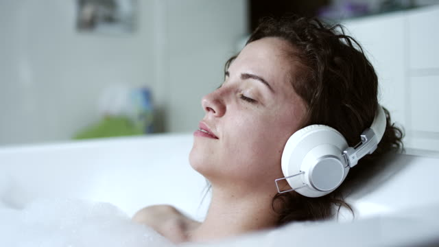 woman listening to music in bathtub - vasca da bagno video stock e b–roll