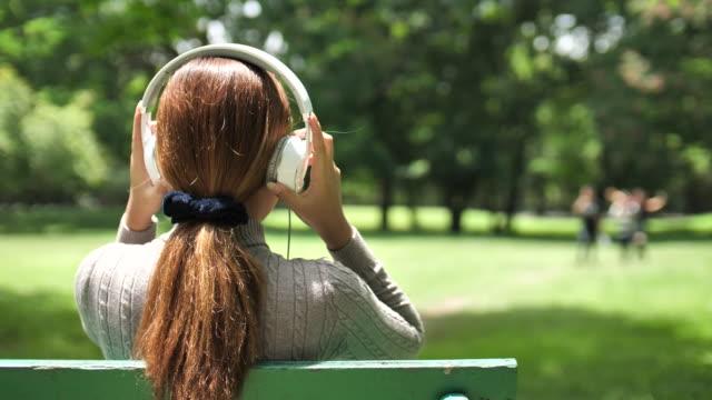vídeos y material grabado en eventos de stock de mujer escuchando música en el parque - detrás
