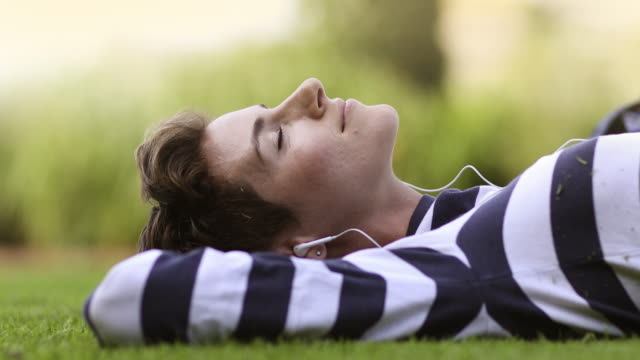 woman listening to music in the park - prato rasato video stock e b–roll