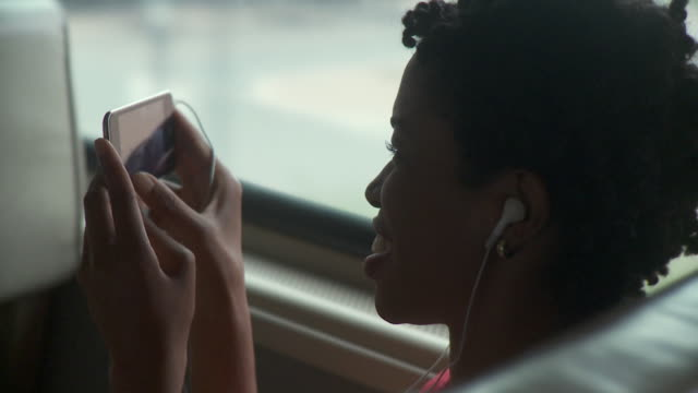 cu woman listening to music on portable media player in moving commuter train / new york city, new york, usa - mp3プレイヤー点の映像素材/bロール
