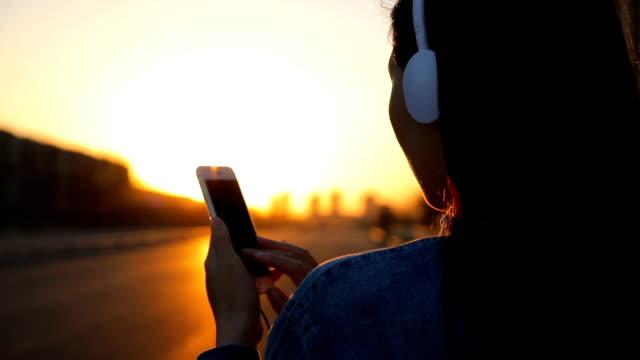 vídeos y material grabado en eventos de stock de woman listening to music with phone at sunset - operar