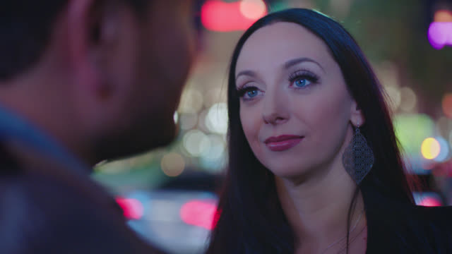 CU OTS. Woman listens and laughs with man under flashing neon lights on Las Vegas strip at night.