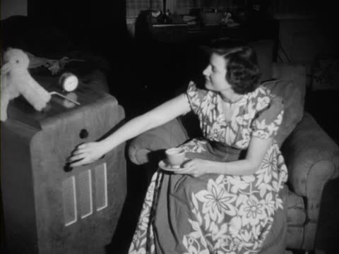 A woman listens to a radio in a living room