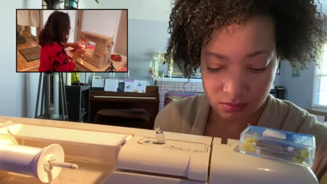 woman listens to and works alongside a sewing video tutorial - craft stock videos & royalty-free footage