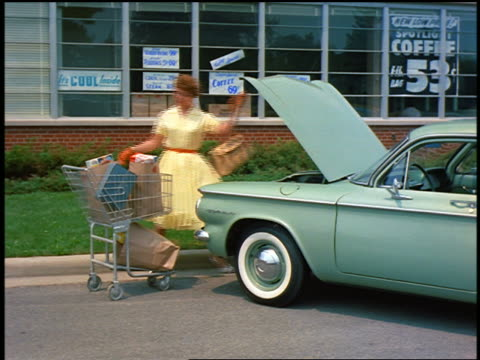 vídeos de stock e filmes b-roll de 1959 woman loading grocery bags into forward trunk of blue corvair - 1950 1959