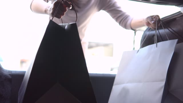 woman loading her car trunk with shopping bags - boot stock videos & royalty-free footage