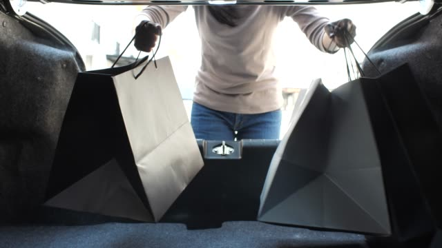 woman loading her car trunk with shopping bags - dentro video stock e b–roll