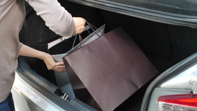 woman loading her shopping bag into car trunk - shopping bag stock videos and b-roll footage