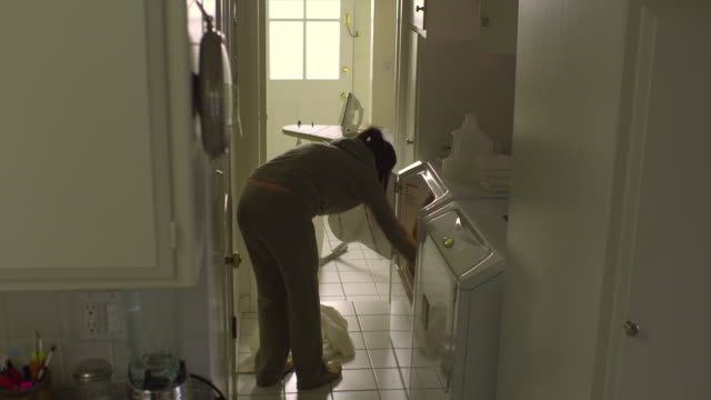 WS, PAN, Woman loading washing machine in laundry room, Hollywood, California, USA