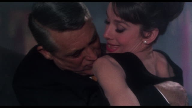 1963 Woman (Audrey Hepburn) locks loving eyes on man (Cary Grant) during orange passing game