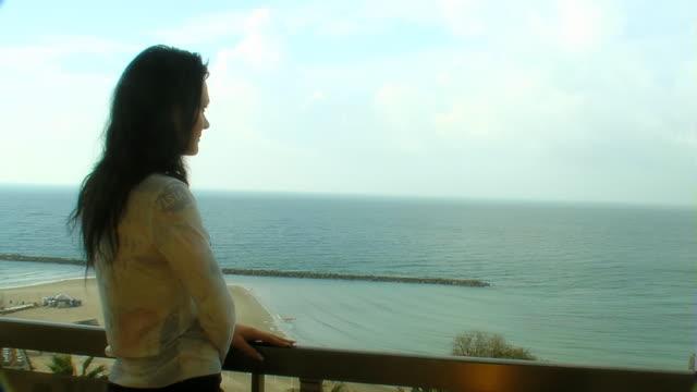 vídeos y material grabado en eventos de stock de mujer mira mar desde el balcón - detalle arquitectónico exterior