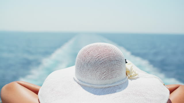 woman looking a ship's wake from the deck - sun hat stock videos & royalty-free footage