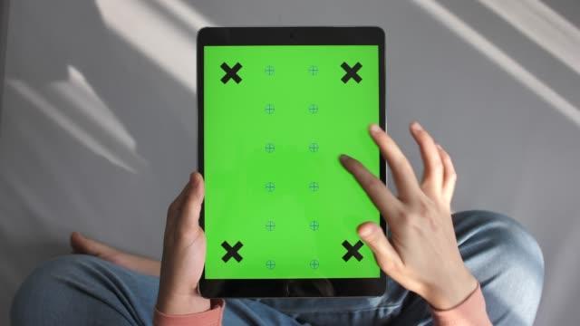 stockvideo's en b-roll-footage met vrouw op zoek en met behulp van digitale tablet met green screen, verticaal - tablet pc
