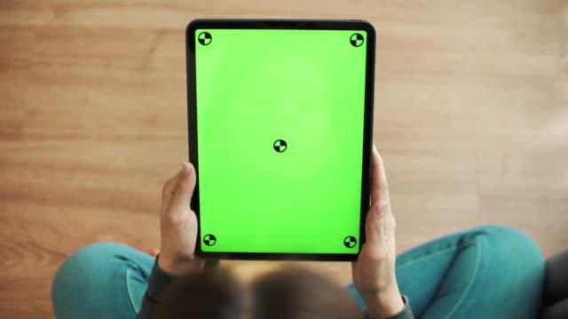 stockvideo's en b-roll-footage met vrouw die en het gebruiken van digitale tablet met groen scherm kijkt en gebruikt - tablet pc