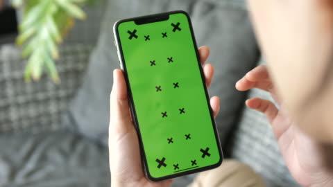 vídeos y material grabado en eventos de stock de mujer mirando y usando la pantalla verde del teléfono móvil - chroma key