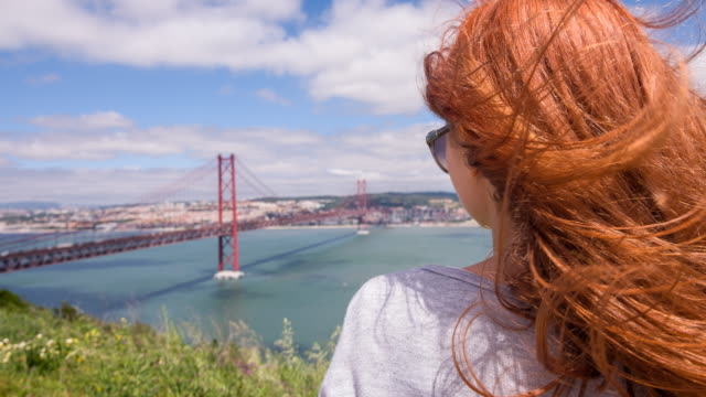 woman looking at 25 de abril bridge in lisbon, portugal - lisbon stock videos and b-roll footage