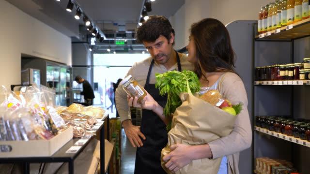 stockvideo's en b-roll-footage met vrouw op zoek naar een product en vriendelijke verkoper biedt zijn hulp om uit te leggen van de eigenschappen van het levensmiddel - glazen pot