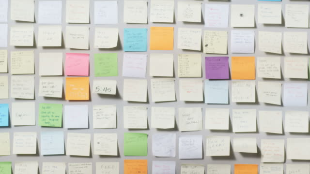 vídeos de stock e filmes b-roll de woman looking at a wall covered in post it notes and pulling one off - cabelo comprido