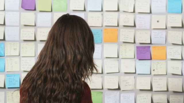 woman looking at a wall covered in post it notes - long stock videos and b-roll footage