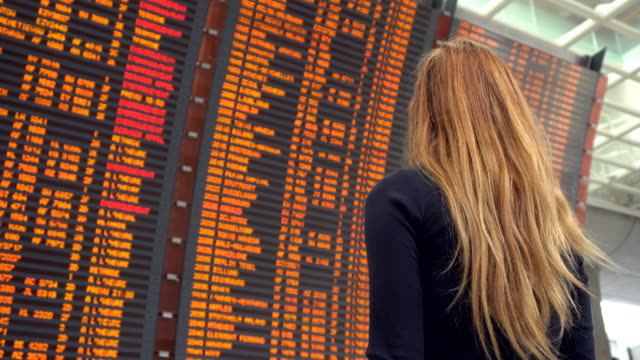 woman looking at airport departure board - aspettare video stock e b–roll