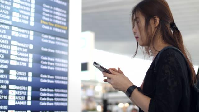 Frau, die am Flughafen Abfahrtstafel