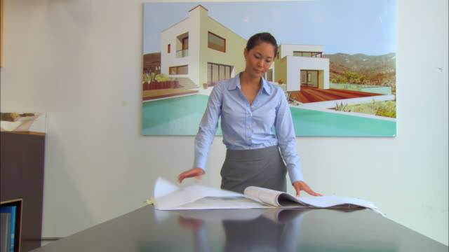 vídeos y material grabado en eventos de stock de ms, woman looking at architectural blueprints, house poster in background - camiseta