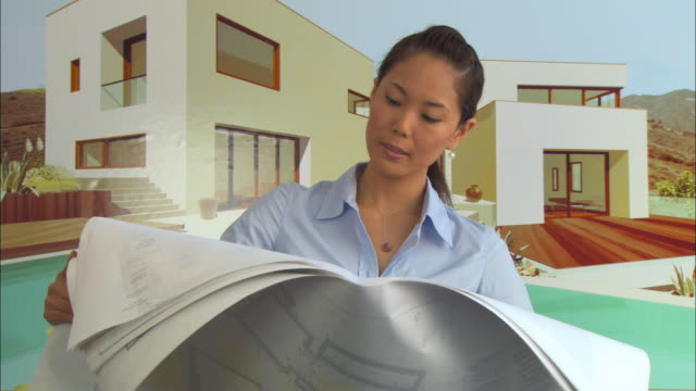 cu, tu, woman looking at architectural blueprints, house poster in background, portrait - poster layout stock videos & royalty-free footage