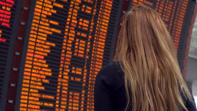 woman looking at arrival departure board - aspettare video stock e b–roll