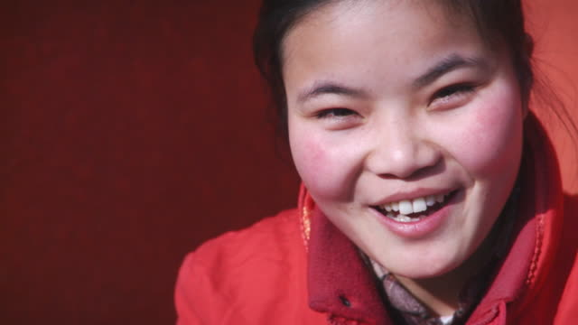 cu slo mo woman looking at camera and smiling / beijing, china - shy stock videos & royalty-free footage